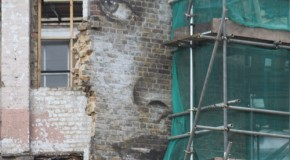 The face of a beautiful woman stares at you from the demolished brick work on Leonard Street, Shoreditch